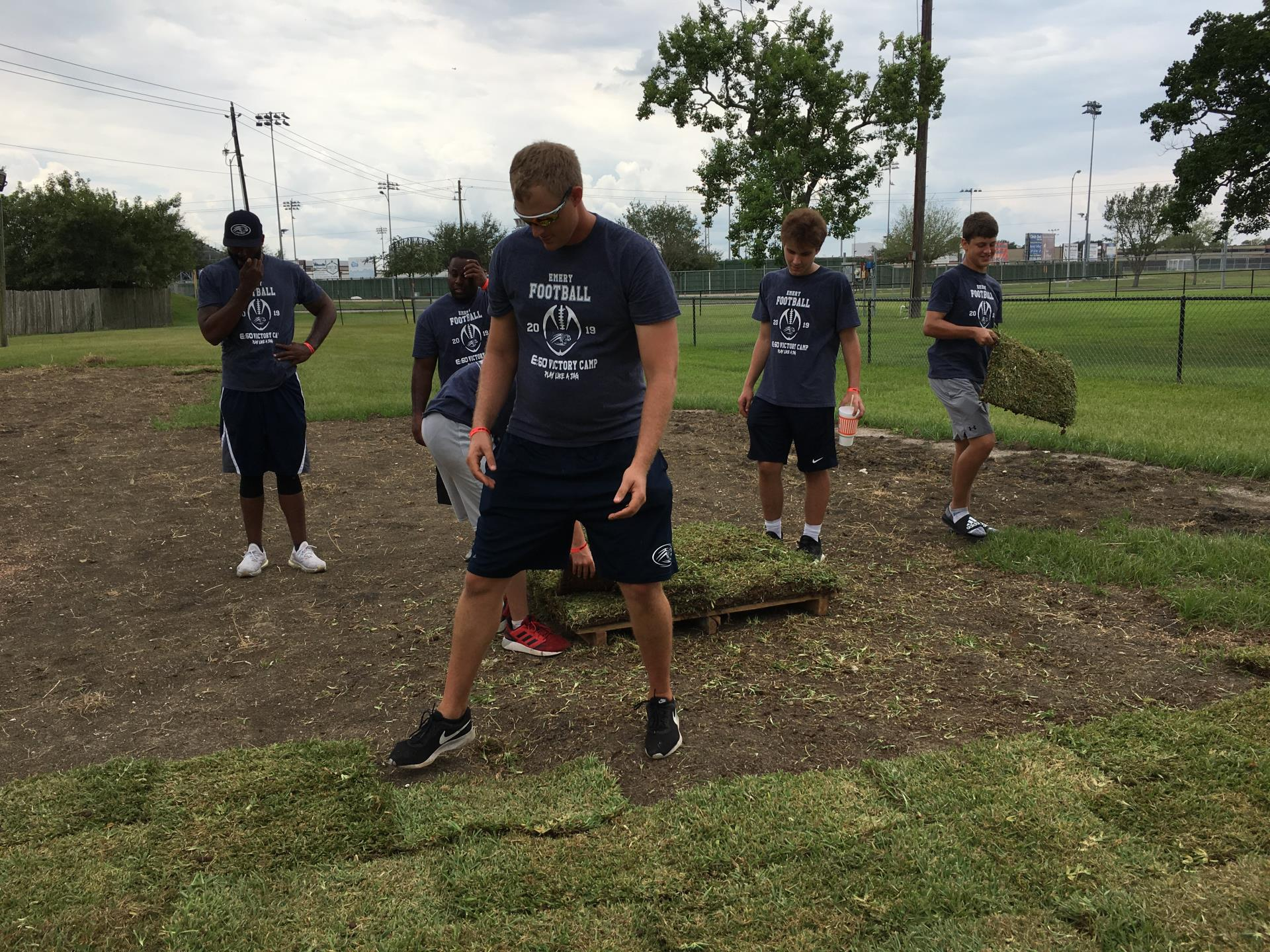 Volunteers from Emery/Weiner High School lay sod at Independence Park dog park.